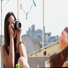 Beautiful woman taking photos of her friends with old fashioned camera Stock Footage