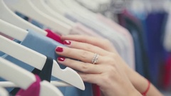 Close-up of female hands plucked a hanger with clothes Stock Footage