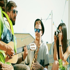 Two guys playing music at the party while girl taking photos and laughing Stock Footage
