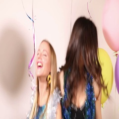 Two young women laughing and dancing in front of white background, photo booth Stock Footage
