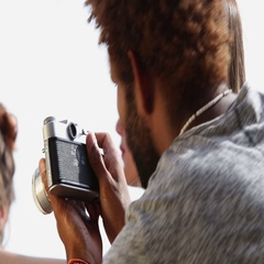 Close up of young man taking photos of his friends with old fashioned camera Stock Footage