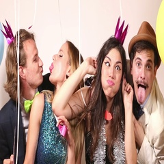 Group of four friends making funny faces in party photo booth Stock Footage