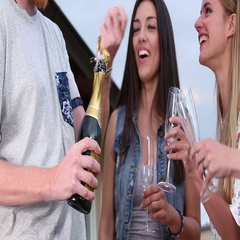 Young ginger man opening champagne, female friends laughing Stock Footage