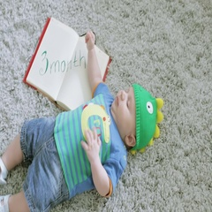 Three-month baby in a green dragon form hat is lying on the grey carpet on back. Stock Footage