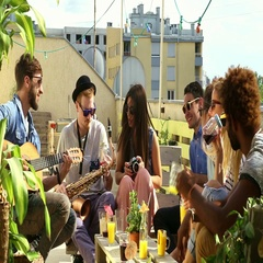 Two guys playing guitar and saxophone, girl taking photos of happy friends Stock Footage