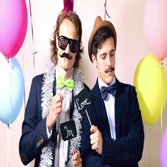 Two cheerful guys holding sign in love in photo booth Stock Footage