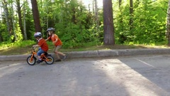 Child teaching his younger brother how to ride a bike Stock Footage