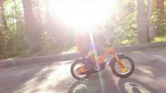 Little boy riding bike fast in summer day. Stock Footage