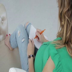 Pregnant woman is writing in a diary while lying on the sofa. Stock Footage