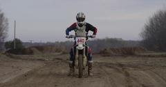 Motocross rider starting up bike Stock Footage