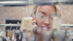 Beautiful girl talking on the phone and smiling. Blonde girl in a shop Stock Footage
