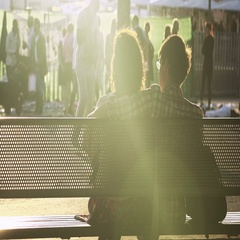 Romantic couple sitting on a bench in the park enjoying the sunny day Stock Footage