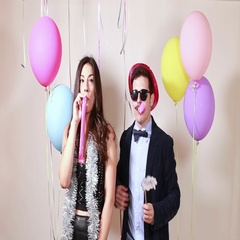 Beautiful couple blowing party horns in photo booth Stock Footage