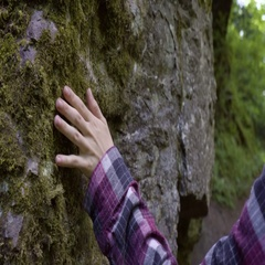 Closeup Of Young Woman Touching A Mossy Cliffside As She Walks Through Stock Footage