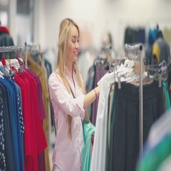 Woman looking at clothes on rail in clothing store. Attractive young woman Stock Footage