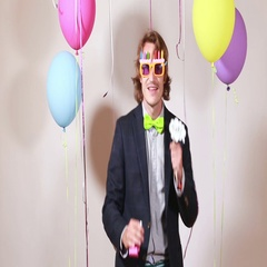 Young man blowing party horn and dancing Stock Footage