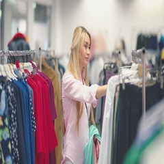 Smiling young woman choosing clothes in a clothing store Stock Footage