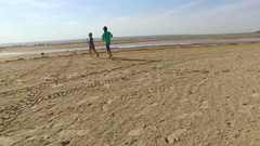 Children playing with soccer ball at the coast Stock Footage
