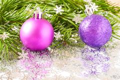 Fir tree branch and Christmas toys bauble and snow flares confetti with copy spa Stock Photos