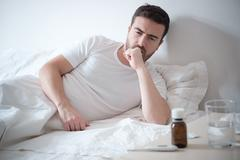 Man feeling bad lying in the bed and coughing Stock Photos