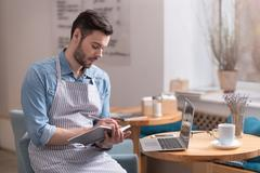 Ambitious man sitting on an armchair and making notes Stock Photos