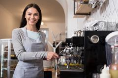 Happy pretty woman using coffee machine Stock Photos