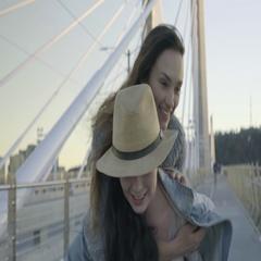Young Women Piggyback Ride On Pedestrian Bridge, Train Goes Past Them Stock Footage