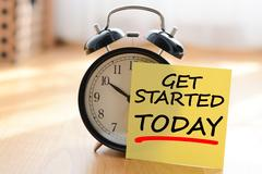 Start today your own business concept with alarm clock and post it message Stock Photos