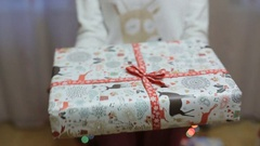 Change Thumbnail Close up a girl gives a gift. Christmas and New Year tree. Stock Footage