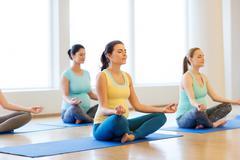 Happy pregnant women exercising yoga in gym Kuvituskuvat