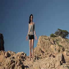 Athletic beautiful girl in yoga pose on top of cliff, natural environment Stock Footage