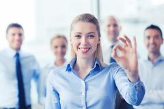 Smiling businesswoman showing ok sign in office Stock Photos