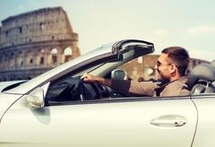 Happy man driving cabriolet car over coliseum Kuvituskuvat