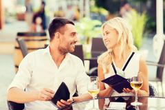 Happy couple with wallet paying bill at restaurant Stock Photos