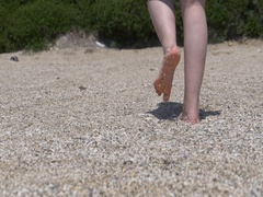 Feet woman walking down a gravel beach and it rests on its feet wet. Stock Footage