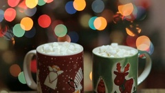 Cups of hot cocoa with marshmallow with Christmas decorations at home Stock Footage