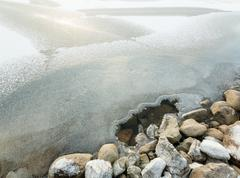 Hole in the ice cover near shore stones at a freezing lake Stock Photos