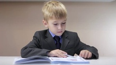 Serious boy writing on his notebook and funny dance Stock Footage