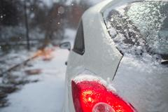 Car covered under white first snow. Red taillight, reverse lights and ice Stock Photos