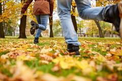 Young couple running in autumn park Stock Photos