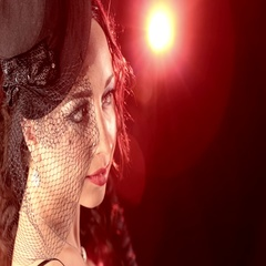 Delicate lady in hat burlesque style against a red spotlight Stock Footage