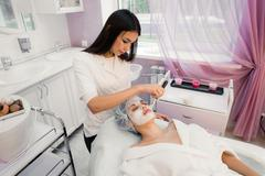 Portrait of young woman while facial cosmetic procedure in spa salon Stock Photos