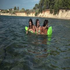Girls having fun in water swimming splashing smiling on blowup mattress Stock Footage
