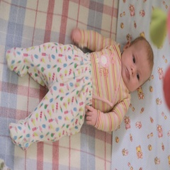 Baby lies in the crib and moves arms and legs Stock Footage