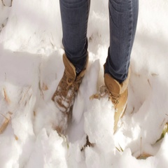Woman in brown shoes joyfully kicking the first snow underfoot Stock Footage