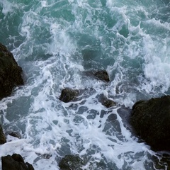 Slow motion of sea swash between boulders. Relax view of water stream Stock Footage