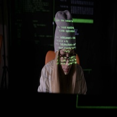 Female hacker working at the computer in dark at night. Binary code projection Stock Footage