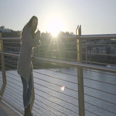 Content Young Woman Leans Against Bridge Railing And Smiles, Backlit By Sunset Stock Footage