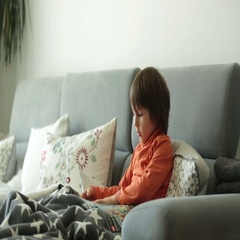 Little boy, reading a magazine, sitting on a sofa, covered with soft blanket Stock Footage