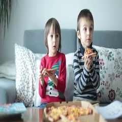 Two children, boys, eating pizza at home while watching TV Stock Footage